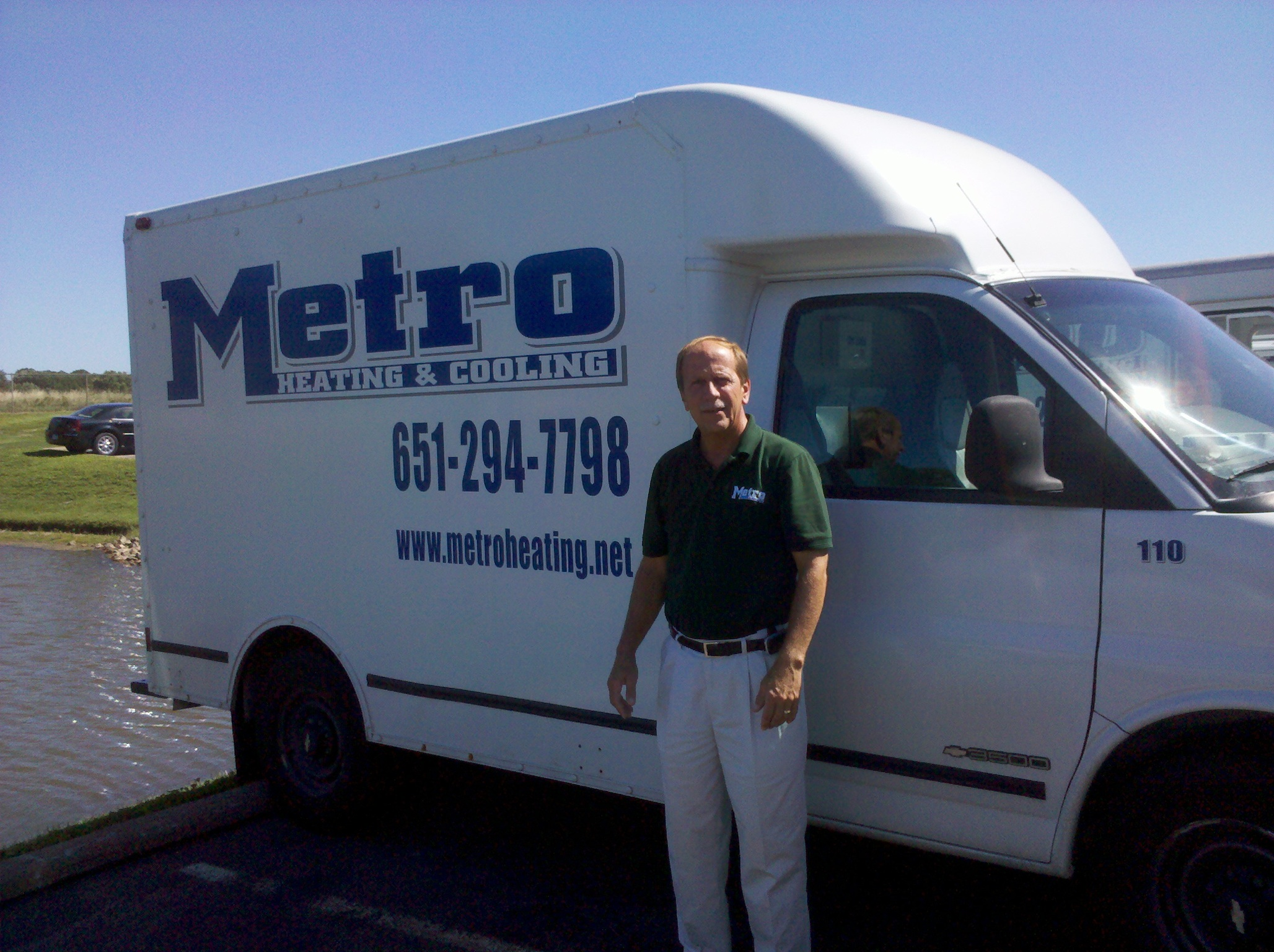 Dave George Reiland standing in front of a Metro Heating & Cooling branded van