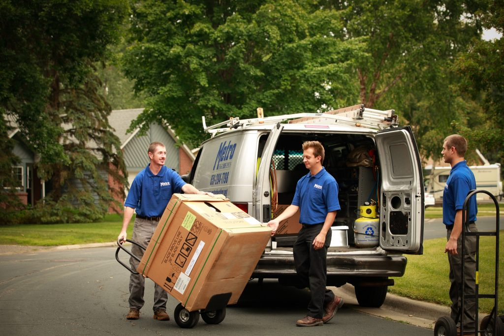 Metro Heating and Cooling Engineers taking an AC unit out of their truck and putting it onto a hand truck